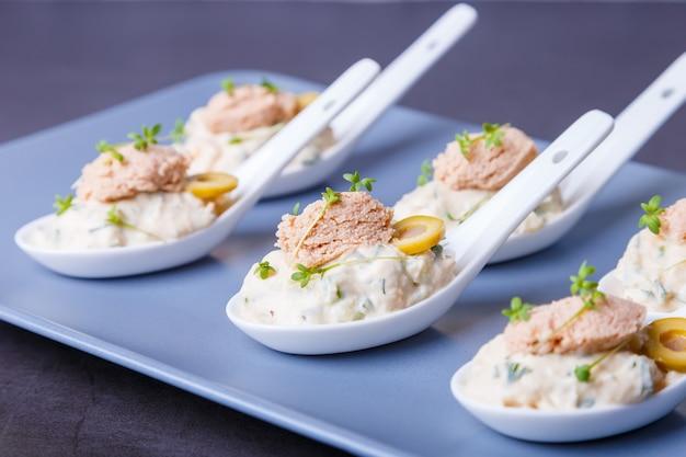 서빙 스푼에 대구 간, 대구 캐비아, 올리브, 오이, 마이크로그린으로 만든 차가운 전채. 전통적인 차가운 요리입니다. 클로즈업, 파란색 접시, 검정색 배경입니다.