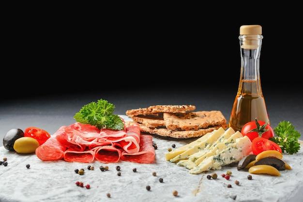 Холодная закуска. ветчина прошутто, салями и голубой сыр с овощами, оливками и ракией