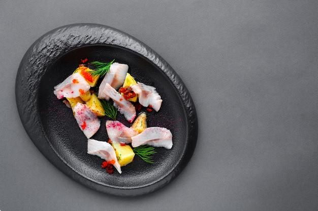 冷製前菜にニシンの塩味と黒皿に茹でたジャガイモ