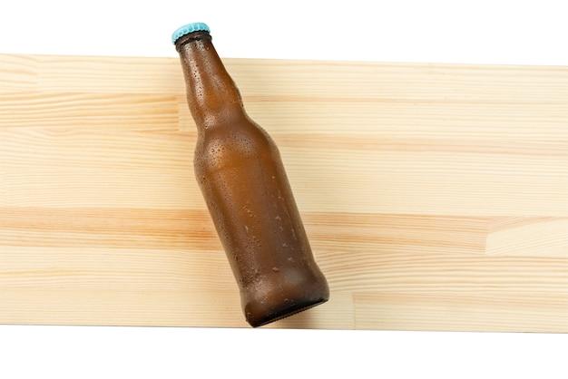Бутылка холодного пива на деревянной доске - вид сверху