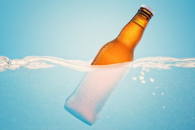 Cold beer in water on blue