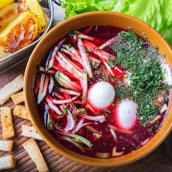 Cold beet soup  quail eggs and cucumbers. top view. closeup
