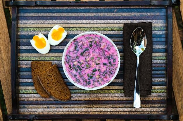 Холодный свекольный суп с яйцом и хлебом на декоративном подносе. суп холодник красный на необычном подносе. еда.