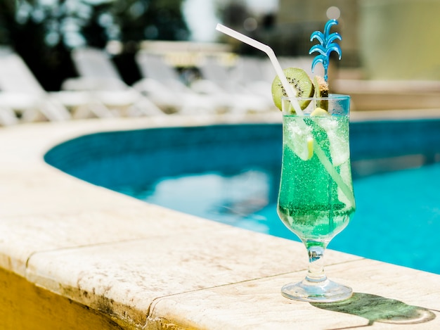 Cold blue cocktail with kiwi and ice near pool