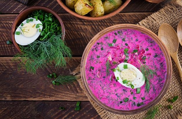 Холодный борщ, летний свекольный суп со свежим огурцом, вареным яйцом и печеным картофелем на деревянном столе. традиционная европейская кухня, вкусный обед. вид сверху, сверху