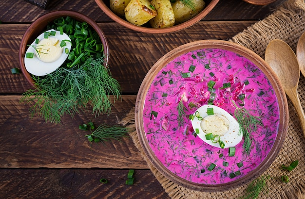 Cold borscht, summer beet soup with fresh cucumber,  boiled egg and baked potatoes on wooden table. traditional european food, delicious lunch. top view, overhead