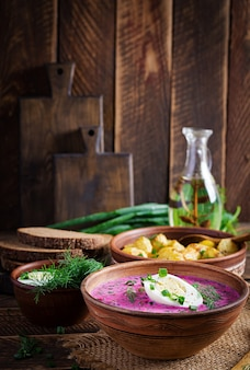Cold borscht, summer beet soup with fresh cucumber,  boiled egg and baked potatoes on wooden table. traditional european food, delicious lunch.