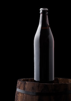 Cold bottle of craft beer on old wooden barrel on black background