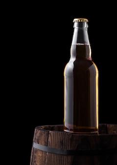 Cold bottle of craft beer on old wooden barrel on black