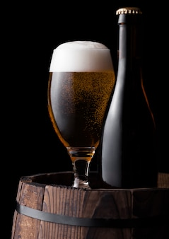 Cold bottle and glass of craft beer on old wooden barrel on black background