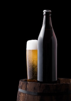 Cold bottle and glass of craft beer on old wooden barrel on black background