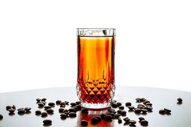 白い背景の上のハイボールグラスで氷と一緒に出される冷たい醸造コーヒーカクテル