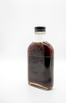 Cold brew coffee in glass bottle with black cap isolated on white