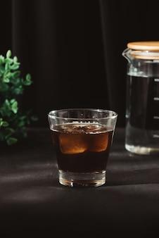 Холодный заварить кофе в стакане на столе