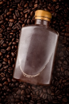 콜드 브루 커피는 병에 담긴 커피 씨앗 더미에, 증기는 병에 달라붙어 떠 있습니다.