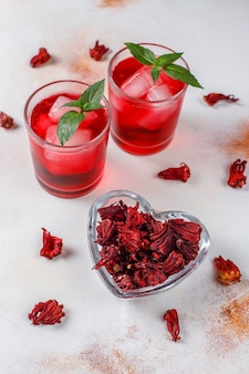 Cold brew hibiscus tea with ice and basil leaves.