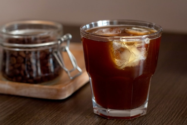 Cold brew ice coffee with ice cubes and jar with coffee beans on wooden plate.