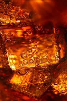 Холодный газированный напиток над кубиками льда в стакане крупным планом