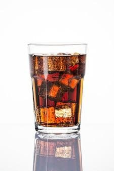 Холодный газированный напиток над кубиками льда в стакане
