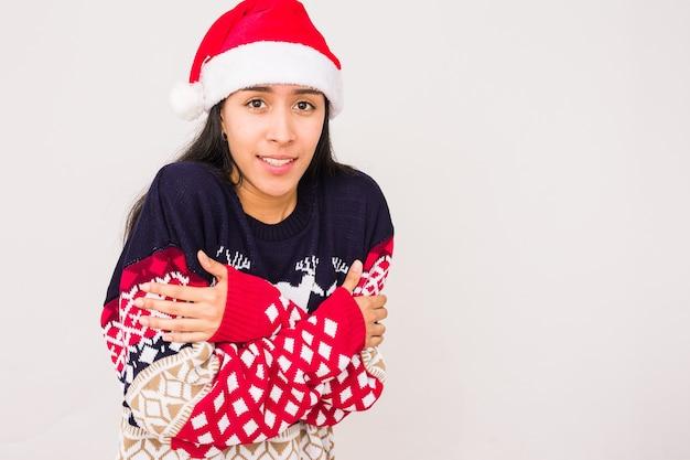 산타 모자와 함께 못생긴 크리스마스 하수를 입고 추운 크리스마스 겨울 라틴 여자