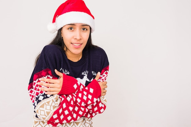 Cold christmas winter latin woman wearing an ugly christmas sewater with santa hat