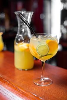 Холодный цитрусовый коктейль с апельсиновым соком и мятой и льдом в стакане с каплями. разноцветный алкогольный коктейль в баре. Premium Фотографии