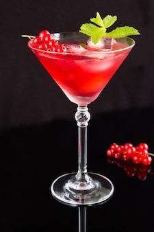 Холодный коктейль с красной смородиной в бокале мартини