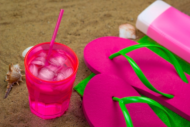 Cold coctail,slippers and sunblock on a green towel on a beach