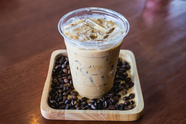 Cold coffee drink frappe or frappuccino in wooden tray with coffee bean on wood table