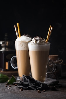 차가운 커피 음료 프라페 또는 프라푸치노, 휘핑 크림 및 초콜릿 칩, 어두운 표면 위에 빨대 포함