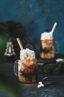 A cold coffee drink with ice and milk in a glass with marshmallows and cookies on a dark background with christmas tree branches.