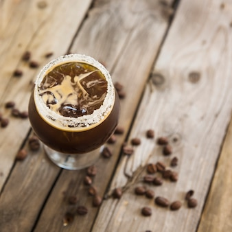 Cold coffee drink with ice on wooden background
