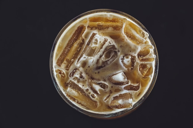 Cold coffee in glass on the dark table in cafe top view