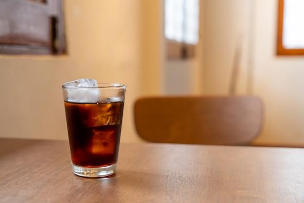 나무 테이블에 아이스 큐브를 가진 차가운 커피 유리
