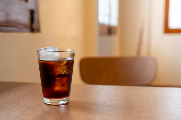 Cold coffee glass with ice cube on wood table