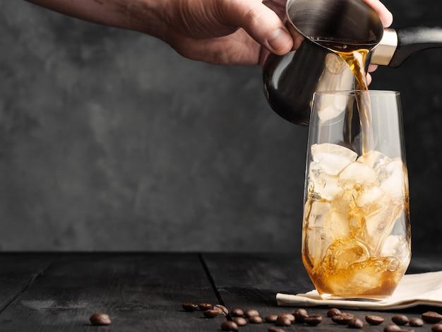 차가운 커피는 터크에서 회색 나무 테이블에 얼음이 든 하이볼 잔에 부어집니다. 아이스 커피.