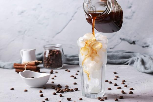 차가운 커피는 밝은 회색 배경에 얼음 조각과 함께 키가 큰 유리 잔에 부어집니다.
