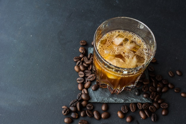 Cold coffee with ice or black russian drink on dark stone surface