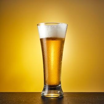 ダークテーブルに滴とガラスの冷たいクラフトライトビール