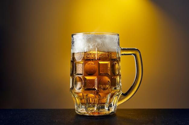 暗いテーブルの上に滴を入れたマグカップの冷たいクラフトライトビール。黄色の背景にビールのパイント。
