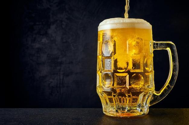 ダークテーブルに滴とマグカップで冷たいクラフトライトビール