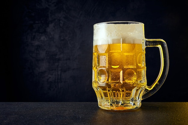 Cold craft light beer in a mug with drops on a dark table. pint of beer on black color background.