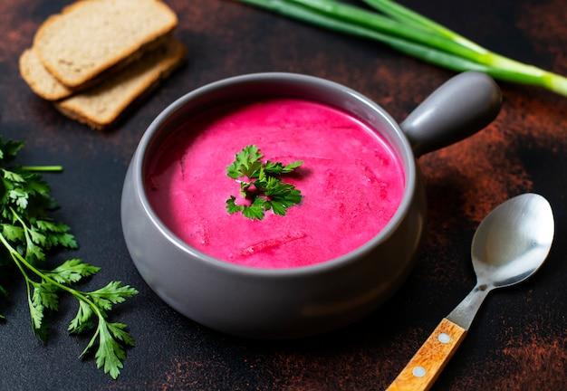 Холодный сливочный суп из свеклы, гаспачо из свеклы. подается в глиняной миске с хлебом и свежими травами. деревенский фон. вегетарианская, чистая еда концепции еды. копировать пространство. закрыть