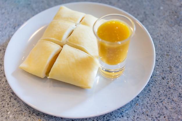 黄色いマンゴーと白いホイップクリームを入れた冷たいクレープにマンゴーソースを添えて