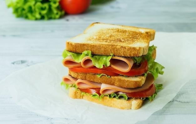 나무 표면에 햄 양상추 토마토와 통 밀에 콜드 컷 칠면조 샌드위치