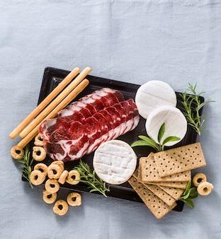 Мясное ассорти и сыр подаются на подносе на столе с белым вином, крекерами, гриссини и таралли с ароматными травами на синей льняной праздничной скатерти.