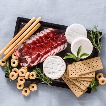 Мясное ассорти и сыр подают на подносе на столе с белым вином, крекерами, гриссини и таралли с ароматными травами на синей льняной праздничной скатерти.