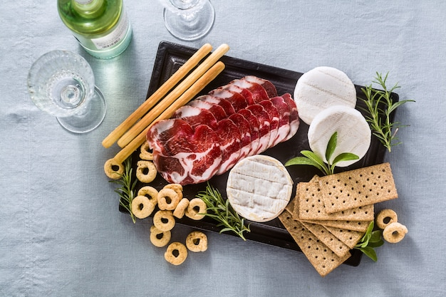 Cold cuts and cheese are served on a tray on a table with white wine, crackers, grissini and taralli with aromatic herbs on a blue linen festive tablecloth.
