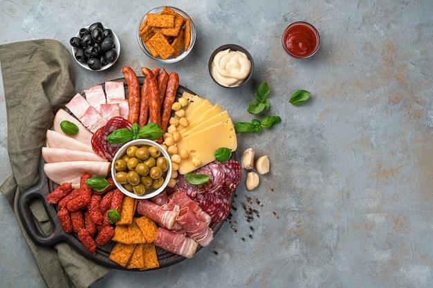 Мясное ассорти, сыр, оливки, крекеры, базилик и соусы на сером фоне.