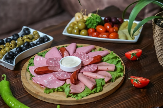 Cold cuts and pickles sausages ham olives tomato cucumber side view